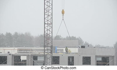 construction site winter - Builders work on residential...