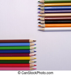 colored pencils lie symmetrically on a neutral background
