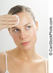 Cleansing Routine - Young beautiful woman cleansing face...