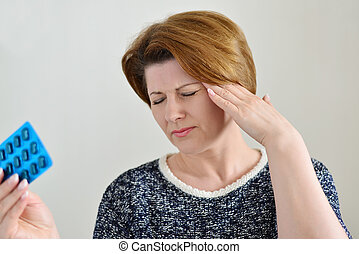 Adult woman taking a pill for headache - Adult woman taking...