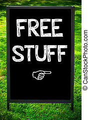 FREE STUFF message on sidewalk blackboard sign against green...