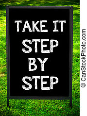 TAKE IT STEP BY STEP message on sidewalk blackboard sign...