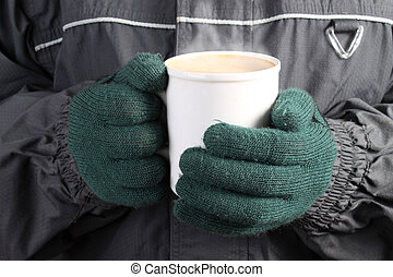 Warm drink in Winter - Person with green mittens, scarf and...