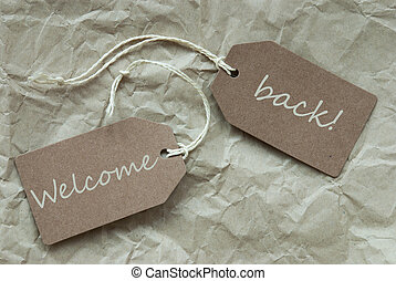 Two Beige Labels With Text Welcome Back Paper Background -...