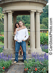 couple - a couple standing under a pillar statue in the park
