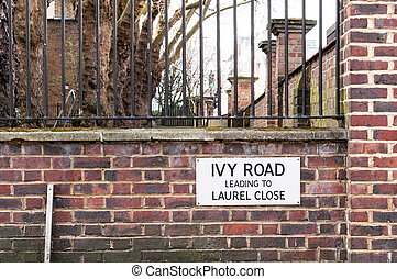 Ivy Road Leading to Laurel Close Street Sign against Brick...