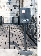Private sign attached to a metal stand wrought iron chain leadin
