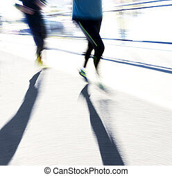 Two back lit joggers in blurred motion in bright sunshine...