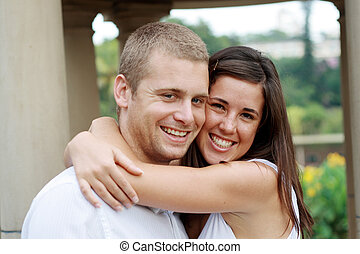 happy young lovers hugging and smiling outdoors