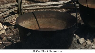 Sap boiling in old metal pots to produce maple syrup during...