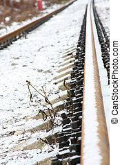 A railroad line covered with snow by a winter day
