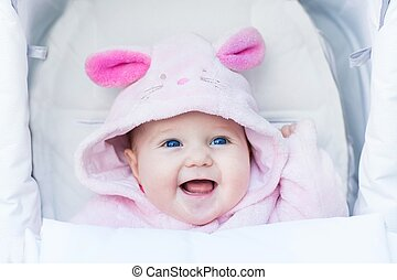 Cute laughing baby girl enjoying a stroller ride on a cold...