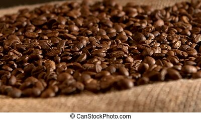 Coffee beans on burlap sacking background, rotation - Brown,...