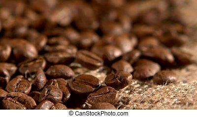 Coffee beans on burlap sacking background, rotation, close...