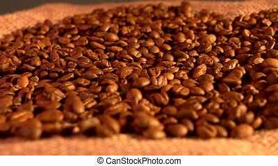 Coffee beans on burlap sacking background, rotation, cam...