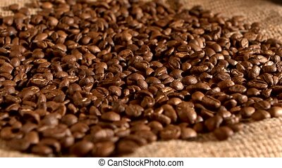 Coffee beans and falling on burlap sacking background,...