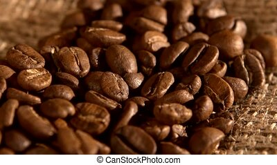 Handful of coffee beans on burlap sacking, background, close...