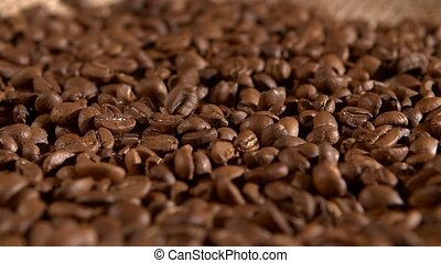 Roasted coffee beans and falling on burlap sacking...