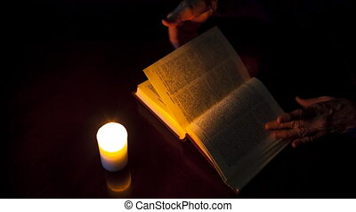 old book on a wooden table by candlelight