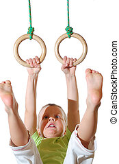 child on gymnastic rinhs - little 4 yea old boy hanging on...
