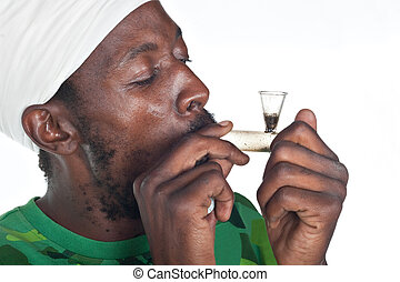 Marihuana smoking - Rastafarian man smoking marihuana from a...