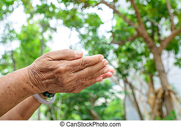 empty senior woman hand holding with bokeh background.