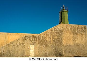 Beacon - Green beacon on top of a concrete wall