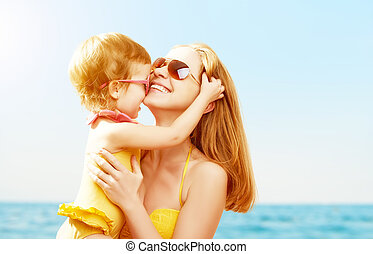 happy family on beach. baby daughter kissing mother - happy...