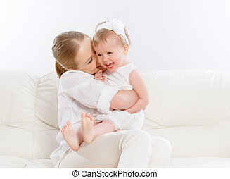 happy family. Mother and baby daughter plays on the sofa -...