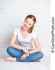 happy young woman is sitting in room with blank wall