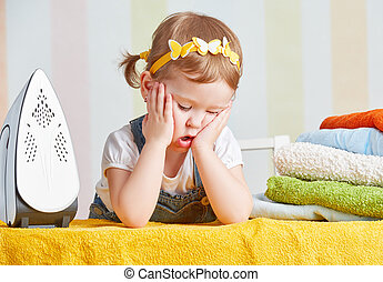 tired cute baby girl housewife iron clothes iron, is engaged...