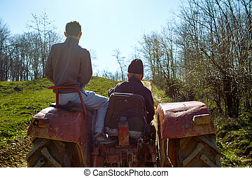 Grandfather and his grandson driving a tractor at sunset -...