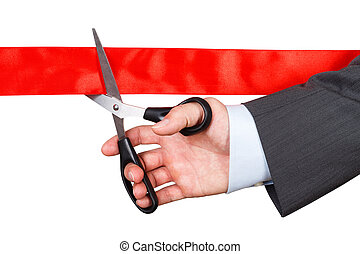 Businessman in suit cutting red ribbon with pair of scissors...
