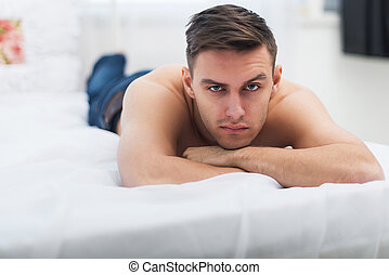 Naked shirtless man in blue jeans lying on his bed at home looking camera