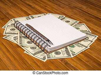 notebook pen Dolar money on a wooden table