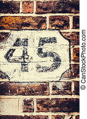 Number 45 painted on brick wall with retro filter applied