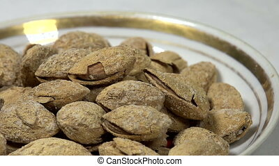 Salted almonds in a Bowl - Front of the camera rotates plate...