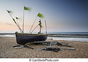 Landscape image of small fishing boats on beach at sunrise...