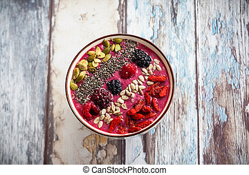 Breakfast berry smoothie bowl topped with goji...