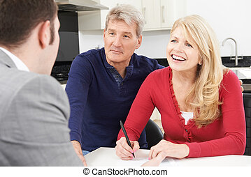 Mature Couple With Financial Advisor Signing Document At Home
