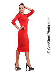Attractive fashion woman wearing a slim red dress walking on...