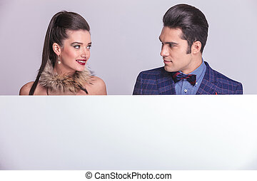 Young fashion man and woman looking at each other
