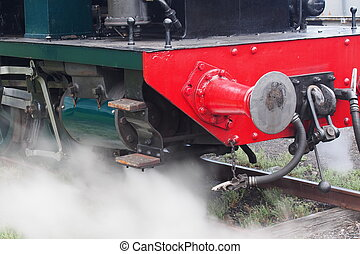 Steaming - A restored old steam train letting off steam near...