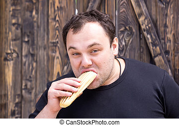 man eating a hot dog - brutal young man eating a hot dog