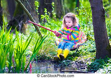 Little girl fishing in a forest - Child playing outdoors....
