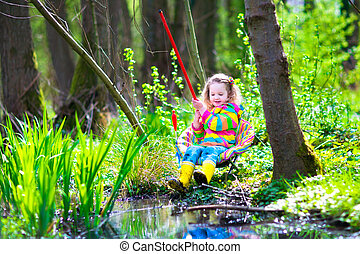 Little girl fishing - Child playing outdoors. Preschooler...