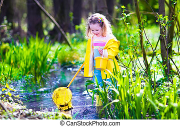 Little girl catching a frog - Child playing outdoors....
