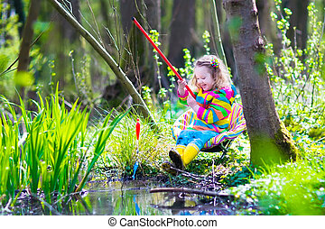 Little girl playing outdoors fishing - Child playing...