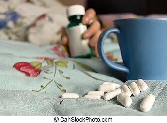 Spilled Pills - Spilled pills, blue cup on a messy bed and...