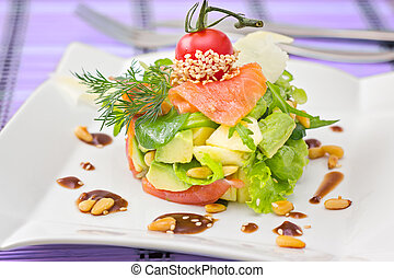 Round shaped Smocked salmon salad with avocado decorated with cherry tomato and tested pine nuts, on purple background